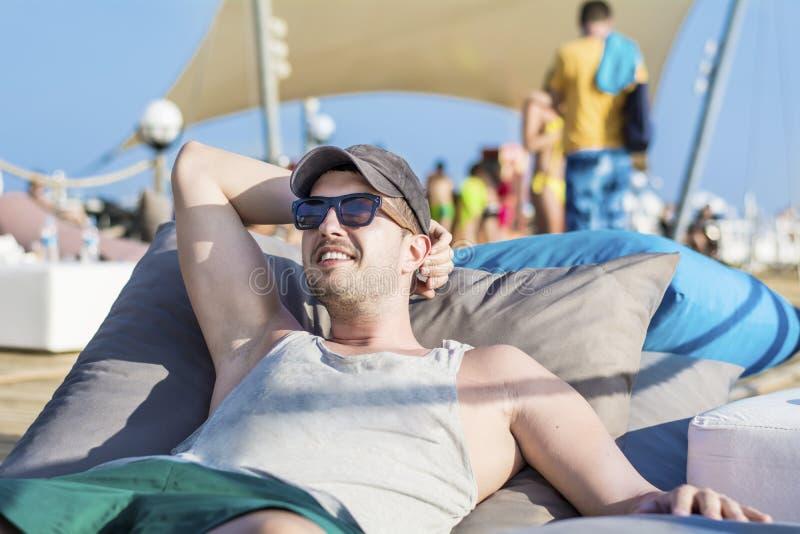 Het jonge knappe mens ontspannen op a sunbed en het kijken het blauwe overzees stock afbeeldingen