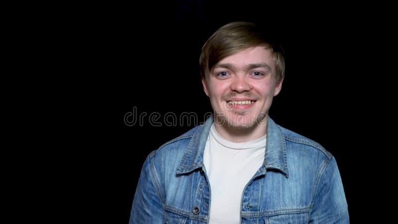 Het jonge knappe model over zwarte achtergrond in een jasje van Jean geeft een vrolijke glimlach De jonge gebaarde mens geeft een royalty-vrije stock foto