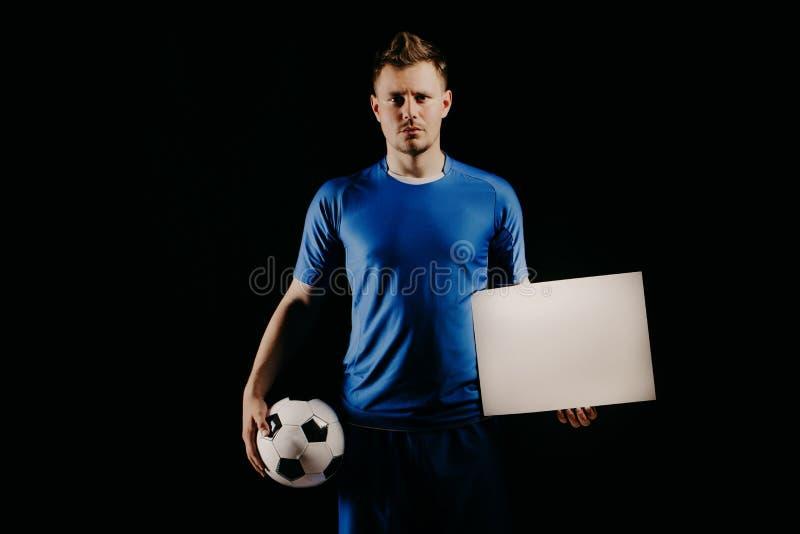 Het jonge knappe voetbalstervoetbal houdt bal en witte spatie op wit stock foto's