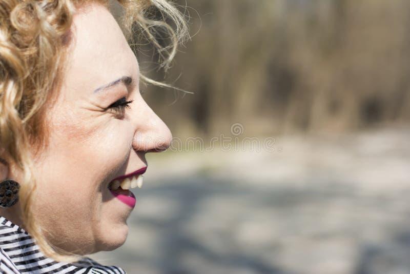 Het jonge krullende blonde vrouw glimlachen royalty-vrije stock afbeeldingen