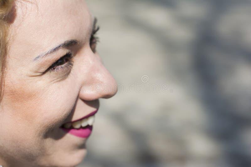 Het jonge krullende blonde vrouw glimlachen stock foto's