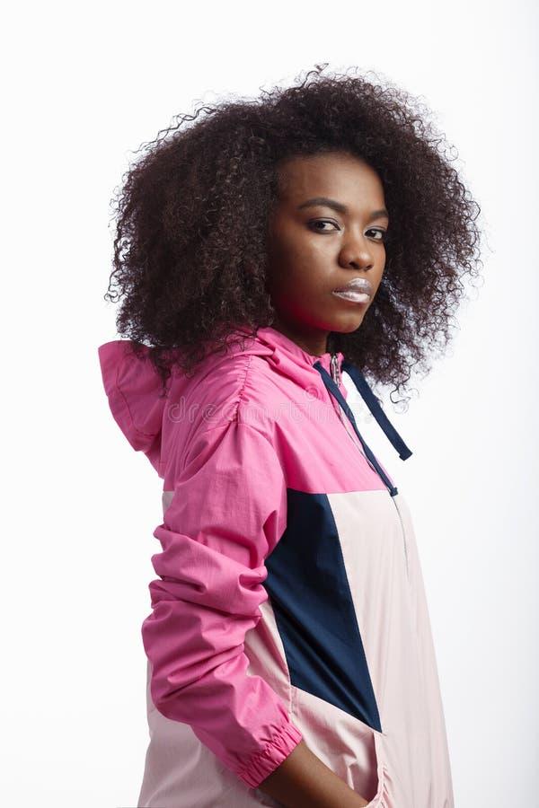 Het jonge krullende bruin-haired meisje kleedde zich in de roze tribunes van het sportjasje bij de witte achtergrond in de studio royalty-vrije stock foto's