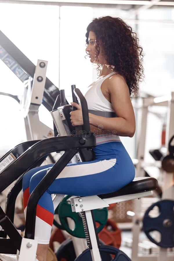 Het jonge krullende goede geschikte meisje gekleed in sportenkleren doet oefening op de sportuitrusting in het moderne gymnastiek royalty-vrije stock foto's