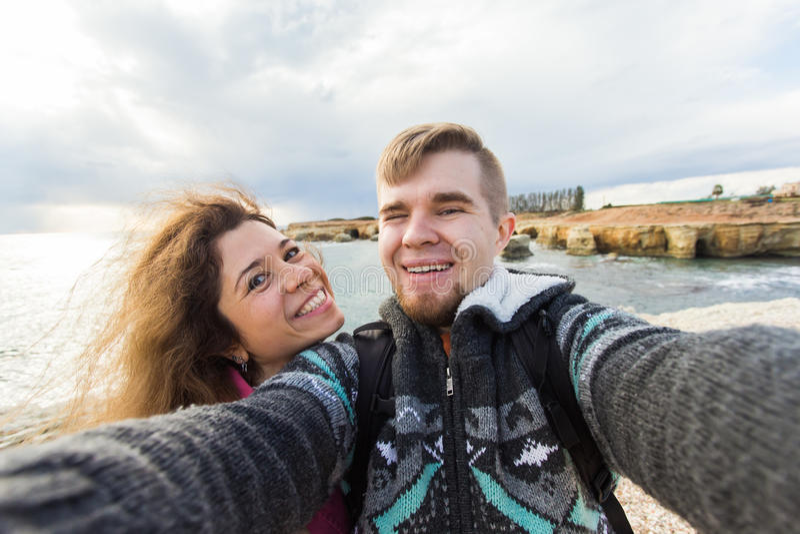 Het jonge het lachen paar wandeling nemen selfie met slimme telefoon Gelukkige jonge man en vrouw die zelfportret met overzees ne royalty-vrije stock afbeelding