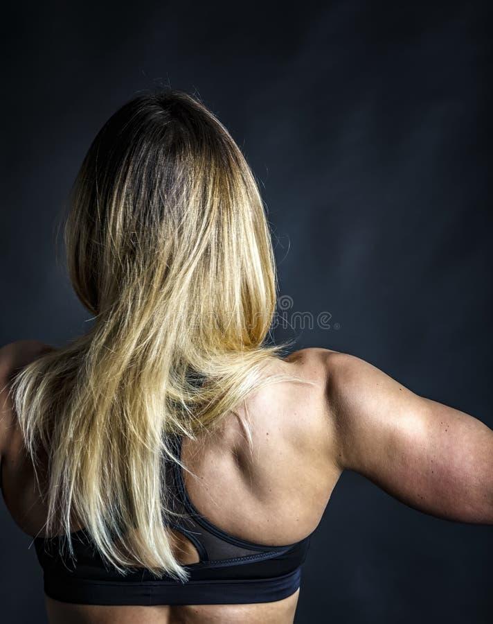 Het jonge lange witte haar van de sportenvrouw toont haar atletisch cijfer Achter mening stock fotografie