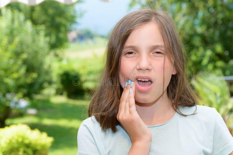 Het jonge leuke kindmeisje heeft een tandpijn royalty-vrije stock foto's