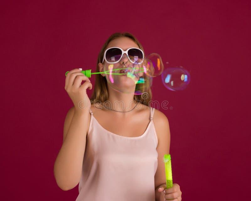 Het jonge leuke meisje blaast geïsoleerde zeepbels, stock afbeelding