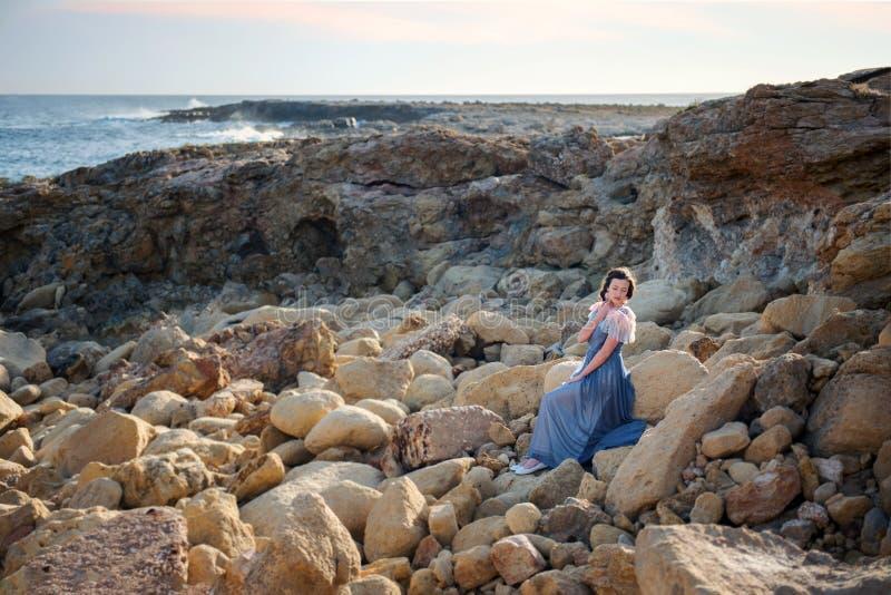 Het jonge leuke meisje zit in zaligheid op de rotsen in het midden van het woedende blauwe overzees stock fotografie