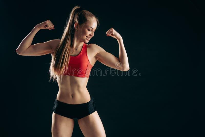 Het jonge leuke ontzagwekkende blonde meisje toont haar wapens en bicepsen stock foto