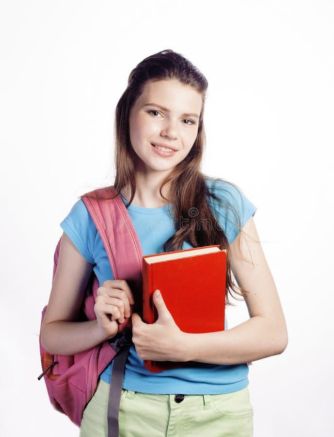 Het jonge leuke tiener stellen vrolijk tegen witte achtergrond met boeken en rugzak stock fotografie