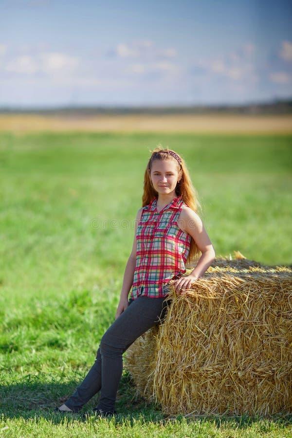 Het jonge leuke tienermeisje stellen dichtbij een hooiberg op het gebied royalty-vrije stock foto