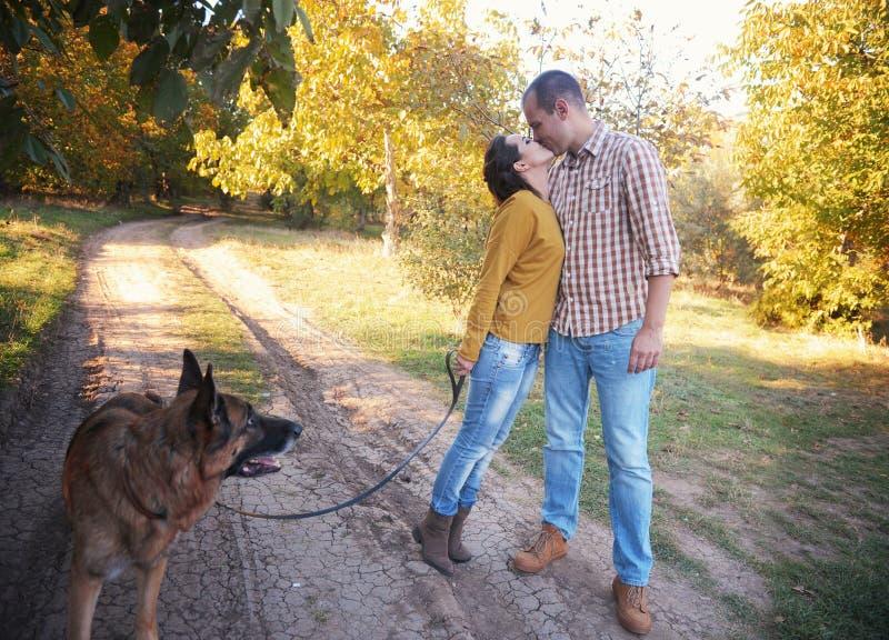 Het jonge liefdepaar die in park met hun Duitse herdershond lopen, heeft een kus royalty-vrije stock foto