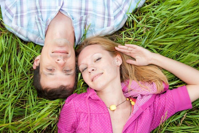 Het jonge liefdepaar legt op groen gras royalty-vrije stock afbeelding