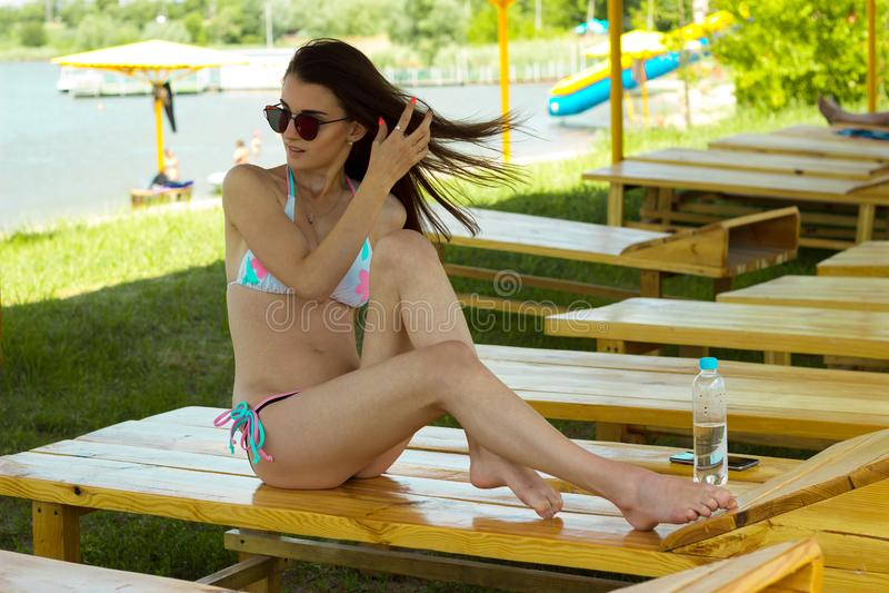 Het jonge magere mooie brunette zit in glazen en een badpak op een strandlanterfanter royalty-vrije stock afbeeldingen