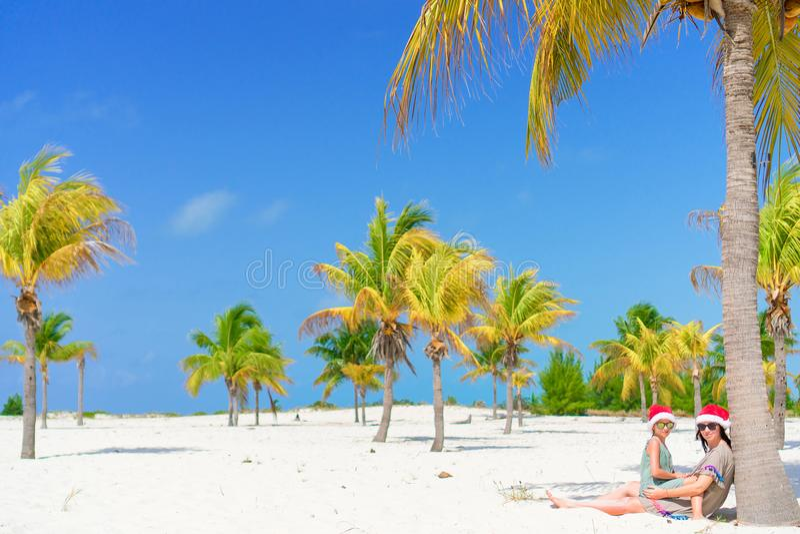 Het jonge mamma en het meisje hebben pret bij tropisch strand in de zitting van de santahoed dichtbij palm royalty-vrije stock foto's