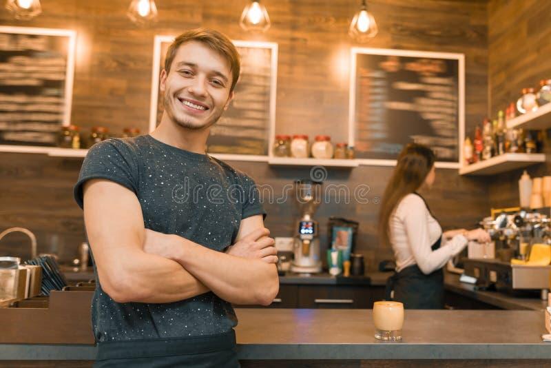 Het jonge mannelijke de winkelarbeider van de baristakoffie glimlachen die de camera met gevouwen die wapens bekijken dichtbij ba stock foto's