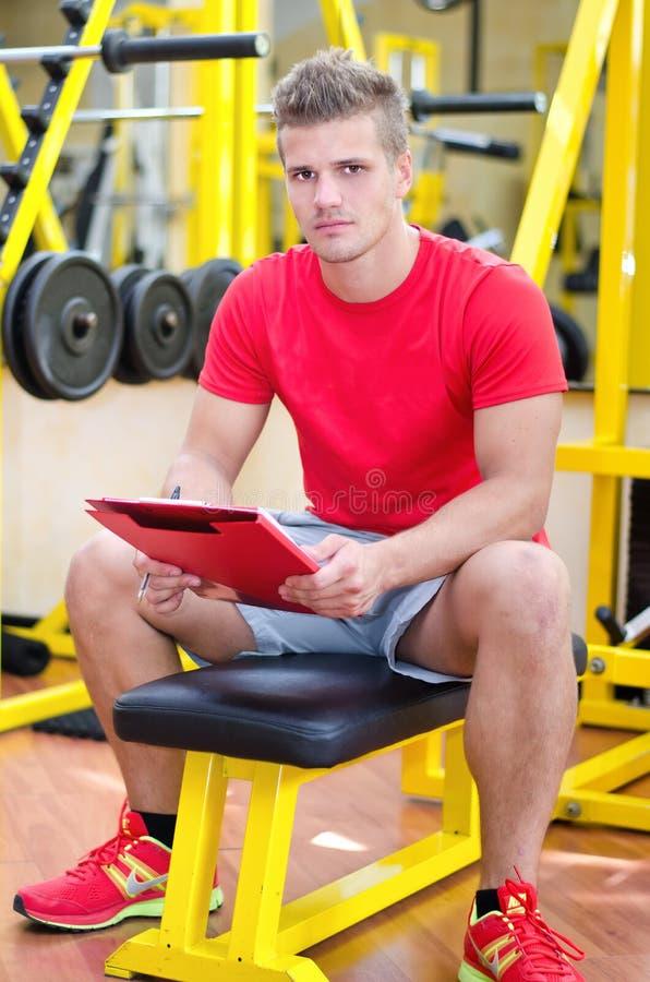 Het jonge mannelijke persoonlijke klembord van de trainerholding stock foto's