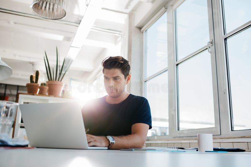 Het jonge mannelijke uitvoerende werken aan laptop bij zijn bureau royalty-vrije stock afbeelding