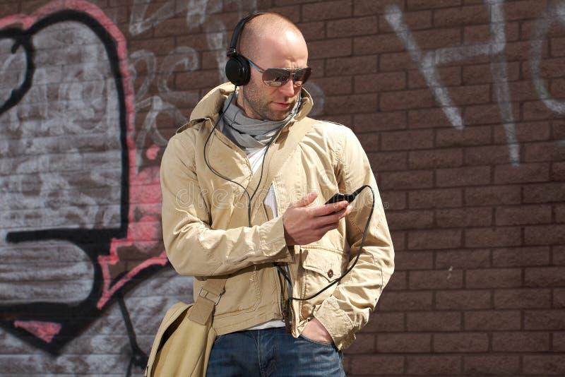 Het jonge mannetje in kaki luistert aan muziek van zijn telefoon royalty-vrije stock afbeelding