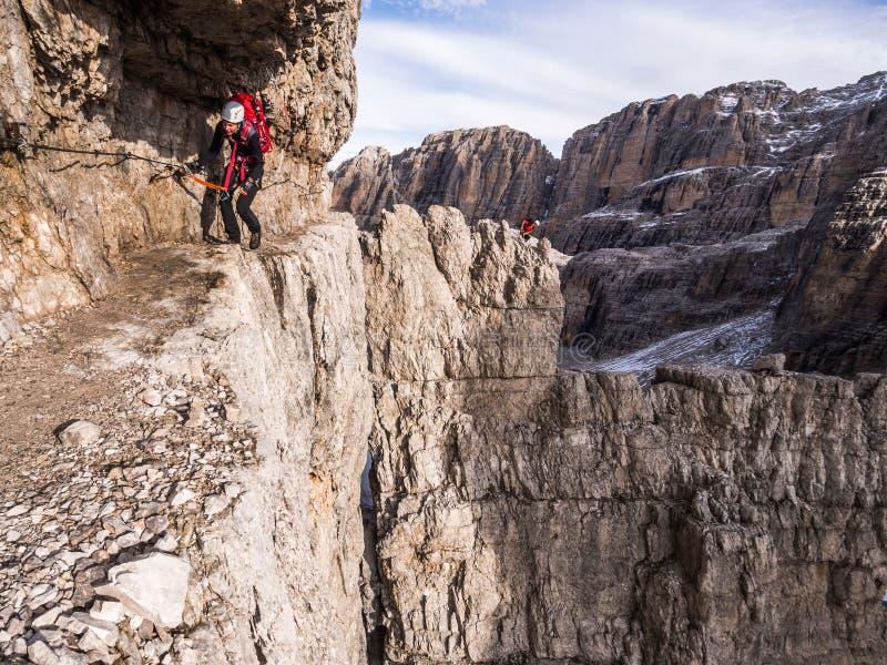Het jonge meisje beklimt via ferratahoogte in de bergen stock foto