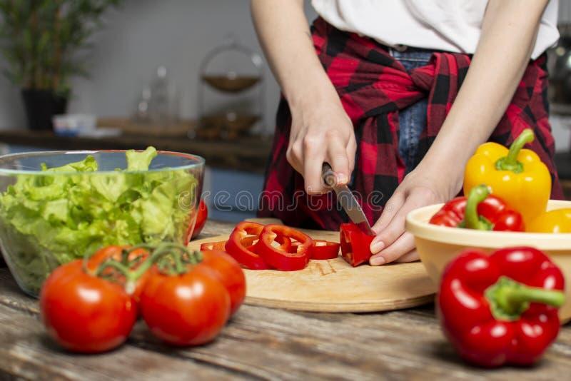 Het jonge meisje bereidt een vegetarische salade in de keuken voor, hakt zij peper, het proces om gezond voedsel, close-up voor t stock fotografie