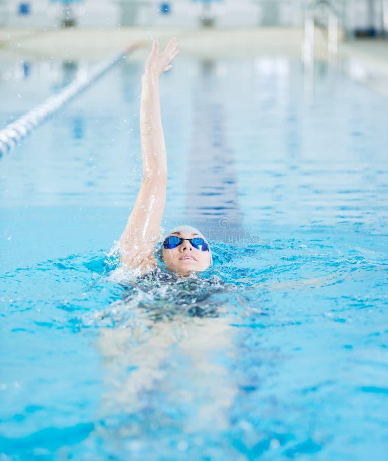 Het jonge meisje in beschermende brillen die terug kruipt slag zwemmen royalty-vrije stock afbeeldingen
