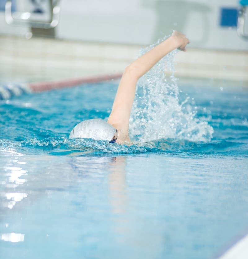 Het jonge meisje in beschermende brillen die voorzijde zwemmen kruipt slagstijl royalty-vrije stock afbeelding