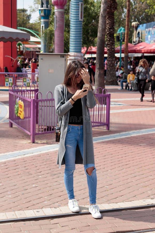 Het jonge meisje bevindt zich en kijkt in haar celtelefoon stock afbeelding