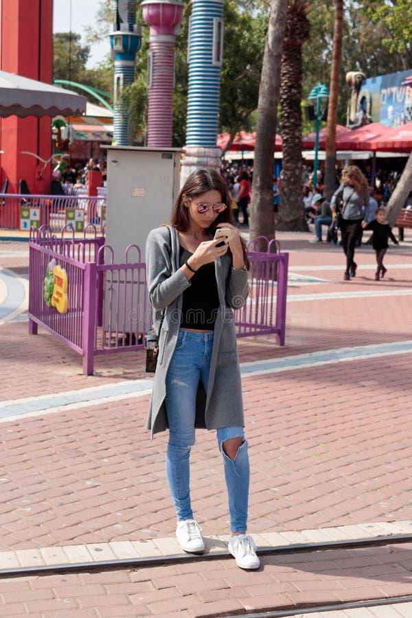 Het jonge meisje bevindt zich en kijkt in haar celtelefoon royalty-vrije stock afbeelding