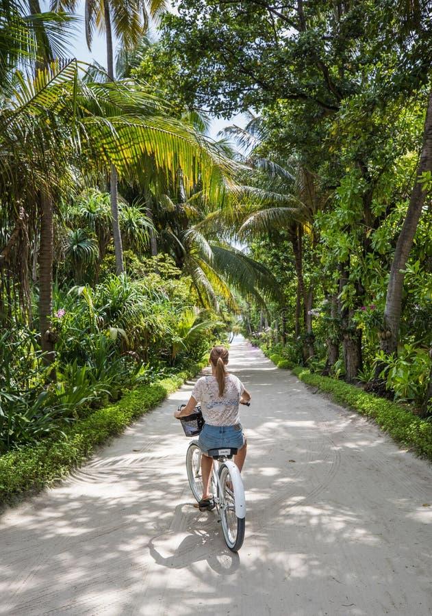 Het jonge meisje bicycling op een tropisch eiland stock afbeeldingen