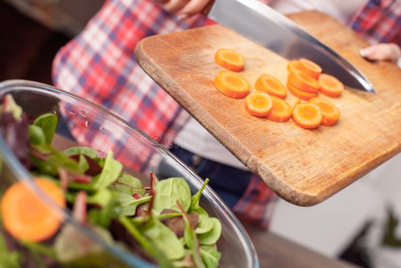 Het jonge meisje bij keuken het gezonde levensstijl bevindende zetten cutted wortel in komclose-up stock fotografie