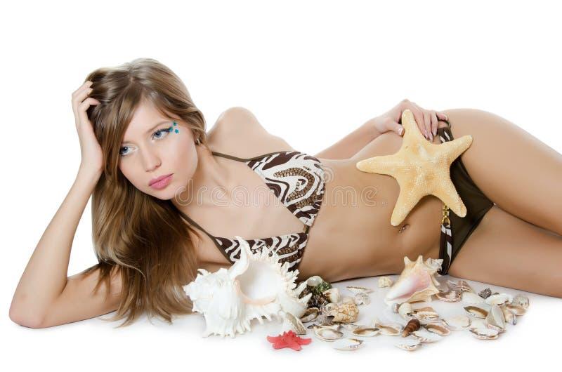 Het jonge meisje in bikini legt met zeeschelpen stock afbeeldingen
