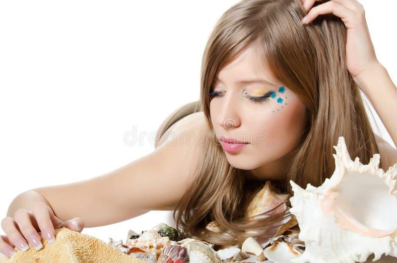 Het jonge meisje in bikini legt met zeeschelpen stock afbeelding