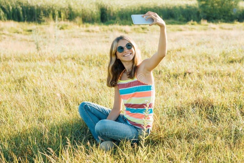 Het jonge meisje blogger neemt foto's en video's voor zijn blog Meisje die op het park van de de zomerstad glimlachen royalty-vrije stock fotografie