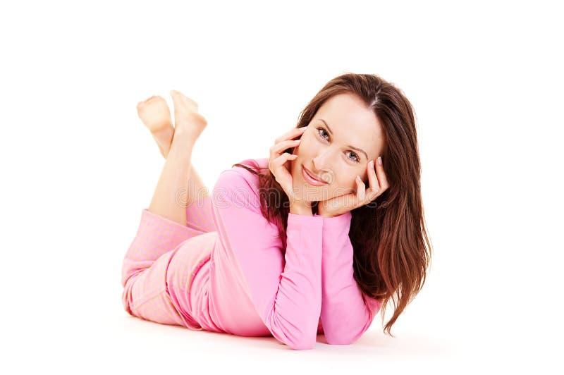 Het jonge meisje dat van Smiley in roze pyjama ligt stock afbeelding