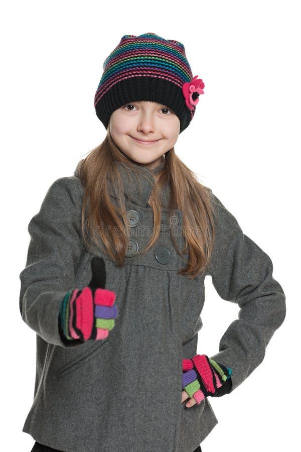 Het jonge meisje in de herfstkleding houdt haar duim tegen royalty-vrije stock fotografie