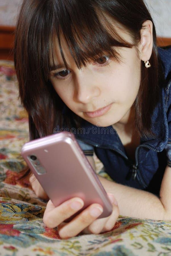 Het jonge meisje de tiener ligt een bed met de celtelefoon Zij communiceert door de mobiele telefoon door middel van boodschapper royalty-vrije stock foto's