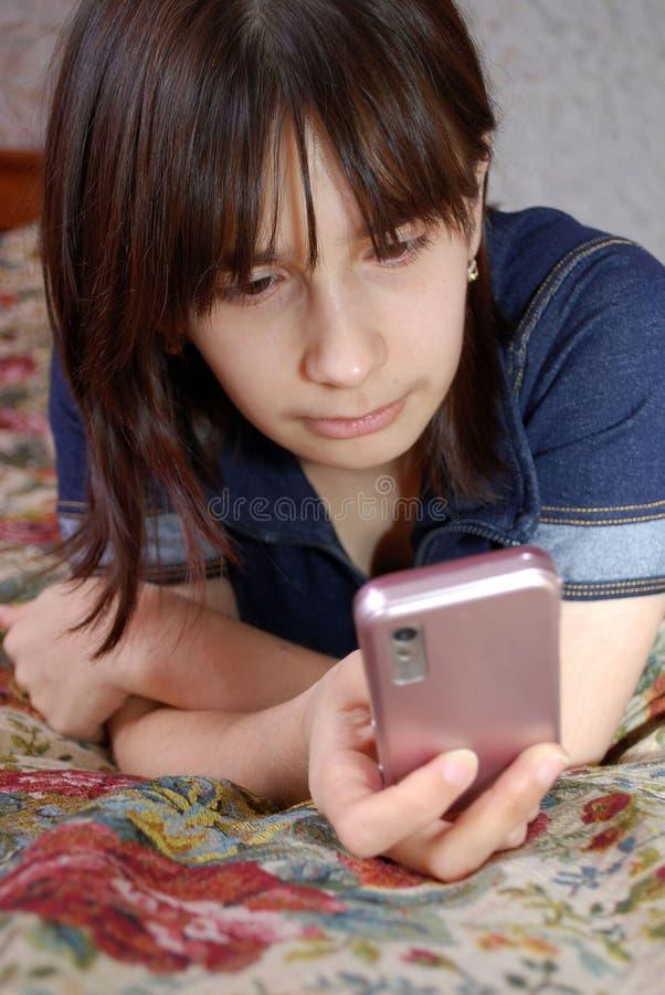 Het jonge meisje de tiener ligt een bed met de celtelefoon Zij communiceert door de mobiele telefoon door middel van boodschapper royalty-vrije stock fotografie