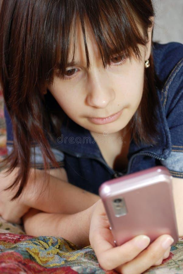 Het jonge meisje de tiener ligt een bed met de celtelefoon Zij communiceert door de mobiele telefoon door middel van boodschapper stock foto