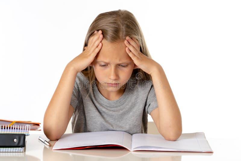 Het jonge meisje die van de schoolstudent ongelukkig en vermoeit in onderwijsconcept kijken die royalty-vrije stock afbeeldingen