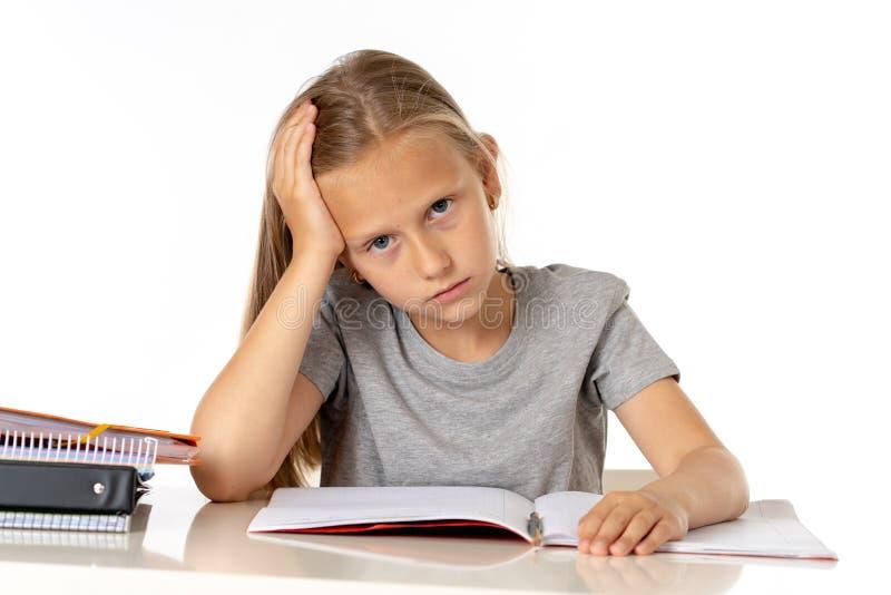 Het jonge meisje die van de schoolstudent ongelukkig en vermoeit in onderwijsconcept kijken die royalty-vrije stock afbeelding