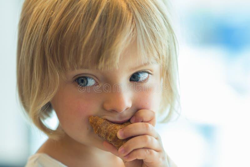 Het jonge meisje die van het baby Kaukasische blonde croissant eten openlucht royalty-vrije stock afbeelding