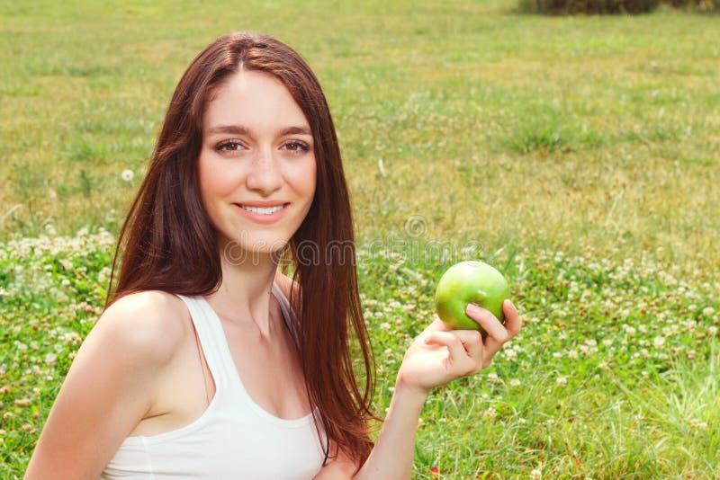 Het jonge meisje die van Nice appel eten stock foto