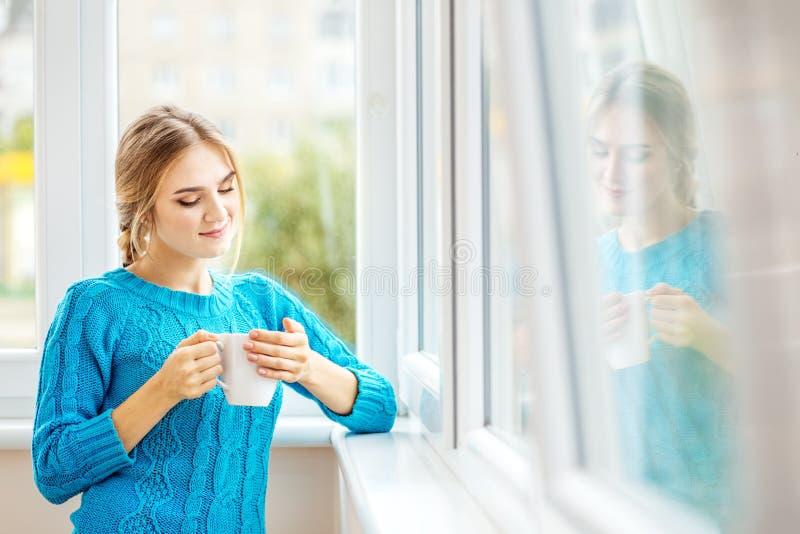 Het jonge meisje drinkt koffie met melk en denkt na Het concept van royalty-vrije stock foto's