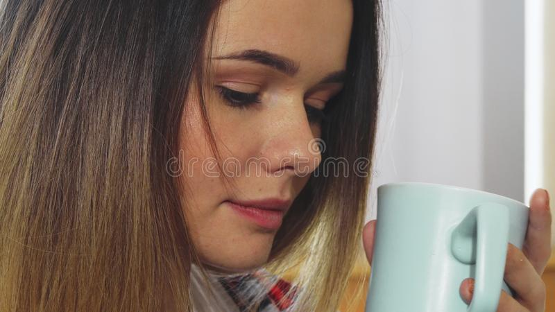 Het jonge meisje drinkt van een mok stock foto