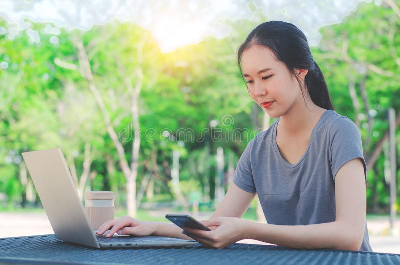 Het jonge meisje is een universitaire student met kop van koffie en een telefoon in haar handen die aan laptop bij de lijst in he royalty-vrije stock fotografie