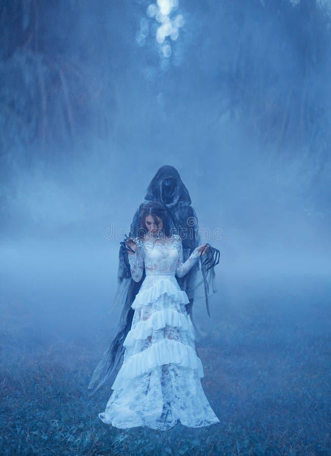 Het jonge meisje in een witte uitstekende kleding en een zilveren halsband bevindt zich op bevroren gras in een dikke blauwe mist stock afbeeldingen