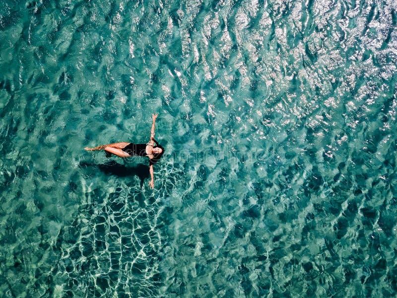 Het jonge meisje in een zwart zwempak zwemt in het overzees stock foto