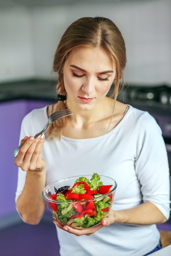 Het jonge meisje eet plantaardige salade Het concept is gezond voedsel, Di stock afbeeldingen