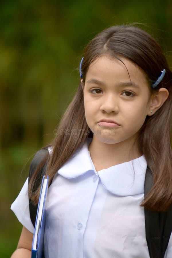 Het jonge Meisje en de Verwarring die van de Minderheidsschool School Eenvormig met Notitieboekjes dragen stock afbeeldingen